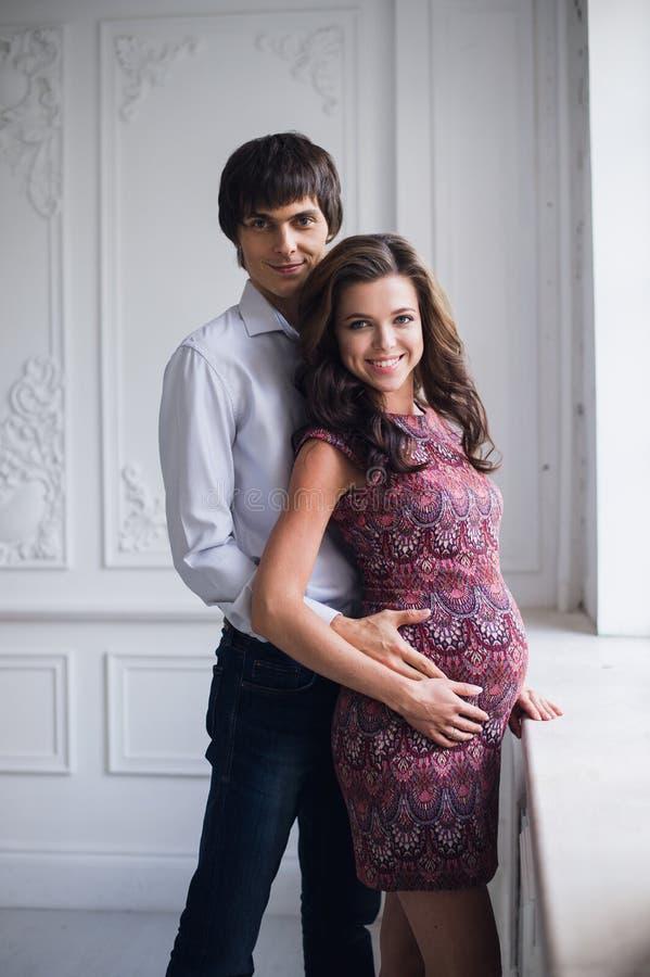 Gravidez e maternidade, conceito dos povos e da expectativa, fim acima da mulher gravida feliz com barriga e seu marido fotografia de stock