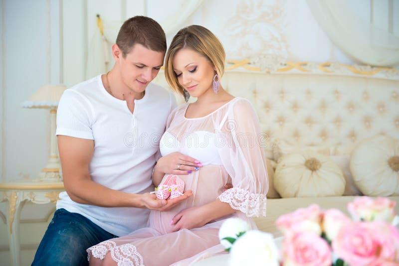 Gravidez feliz: marido que guarda montantes do bebê perto da barriga sua esposa grávida fotografia de stock royalty free