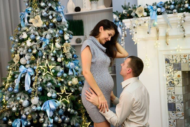 Gravidez, feriados de inverno e conceito dos povos - esposa grávida feliz com marido em casa no Natal Família nova fotos de stock royalty free