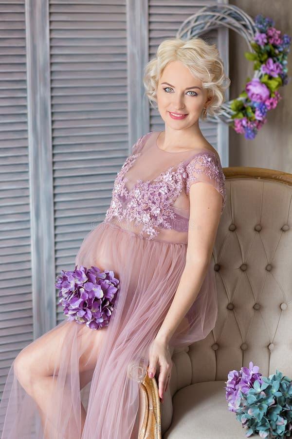 Gravidez, maternidade e conceito futuro feliz da mãe - mulher gravida no vestido violeta pairoso com as flores do ramalhete contr fotografia de stock royalty free