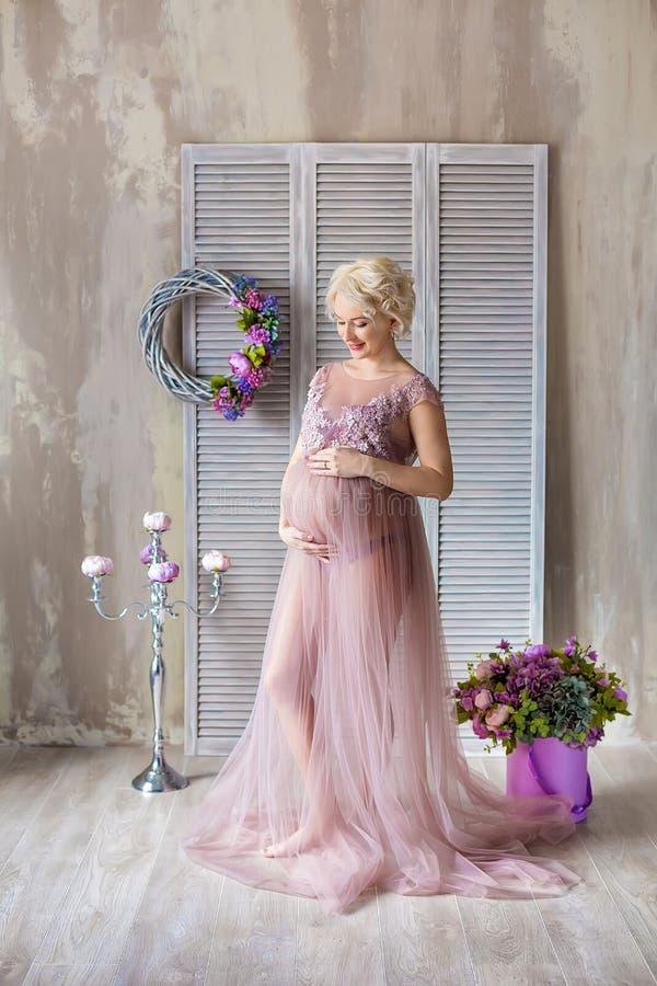 Gravidez, maternidade e conceito futuro feliz da mãe - mulher gravida no vestido violeta pairoso com as flores do ramalhete contr imagens de stock