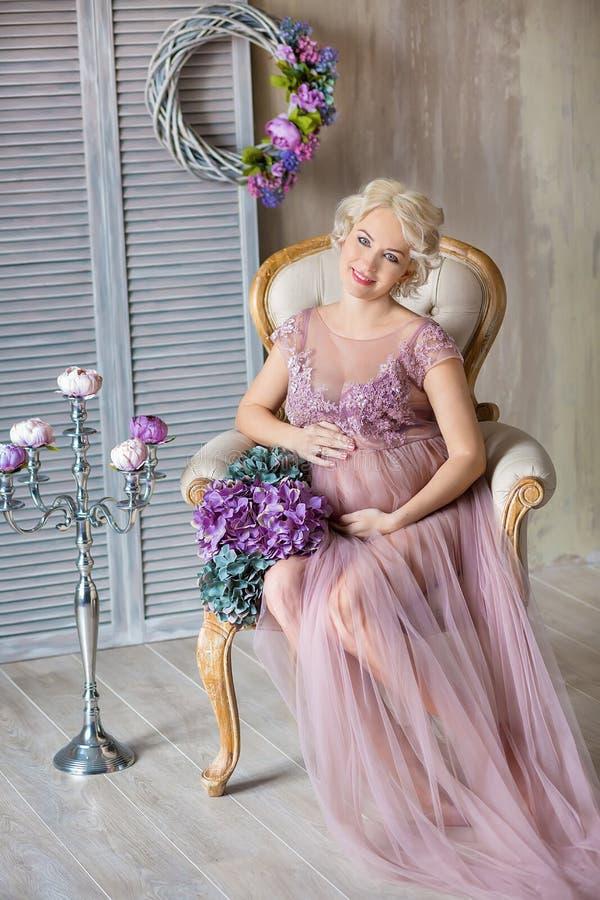 Gravidez, maternidade e conceito futuro feliz da mãe - mulher gravida no vestido violeta pairoso com as flores do ramalhete contr imagens de stock royalty free