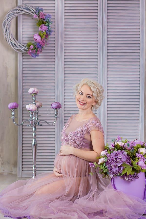 Gravidez, maternidade e conceito futuro feliz da mãe - mulher gravida no vestido violeta pairoso com as flores do ramalhete contr imagem de stock royalty free