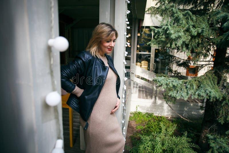 Gravidez, maternidade e felicidade Fêmea grávida nova à moda que tem o resto no parque Mulher bonita que espera o bebê, apreciand imagem de stock royalty free
