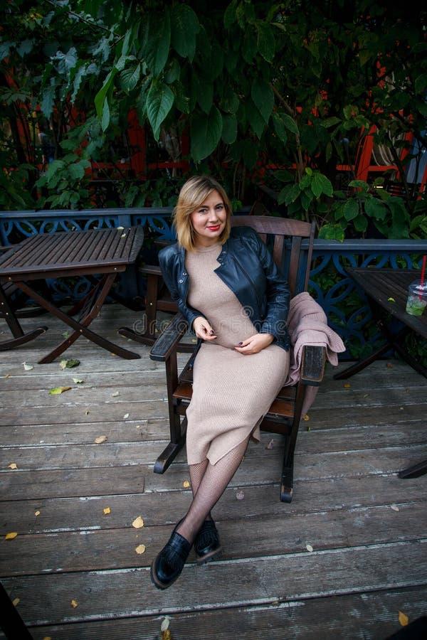 Gravidez, maternidade e felicidade Fêmea grávida nova à moda que tem o resto no parque, sentando-se no armcheir de madeira Mulher foto de stock