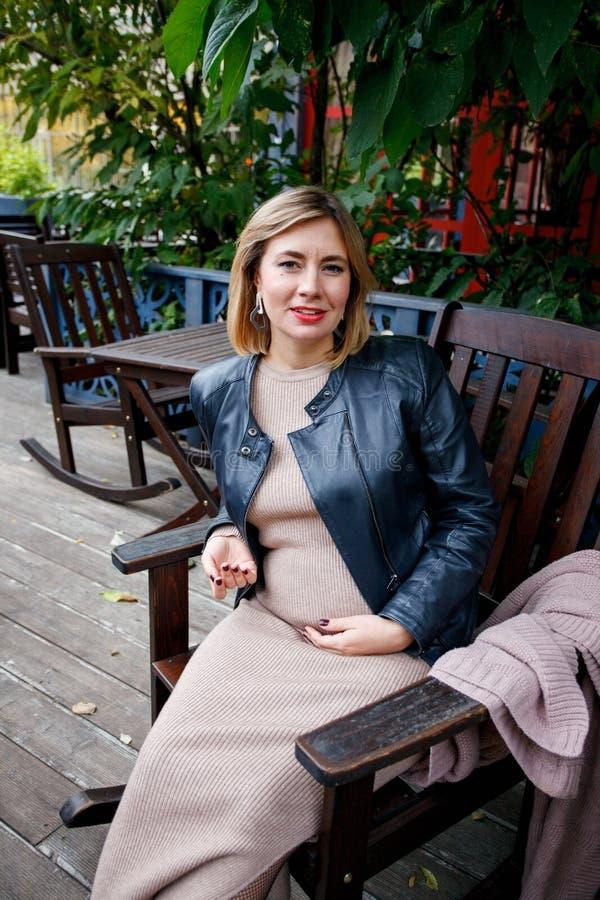 Gravidez, maternidade e felicidade Fêmea grávida nova à moda que tem o resto no parque, sentando-se no armcheir de madeira Mulher fotos de stock
