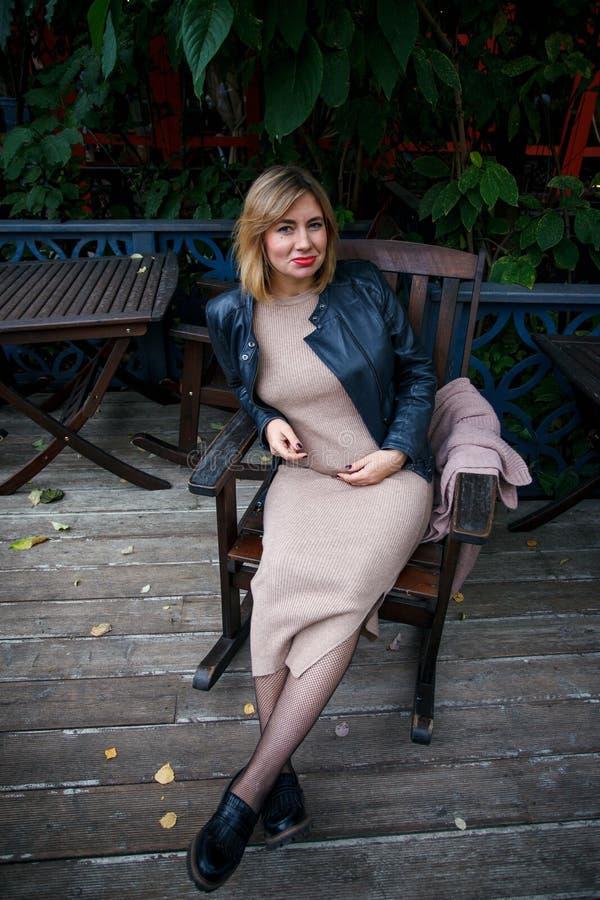 Gravidez, maternidade e felicidade Fêmea grávida nova à moda que tem o resto no parque, sentando-se no armcheir de madeira Mulher fotos de stock royalty free
