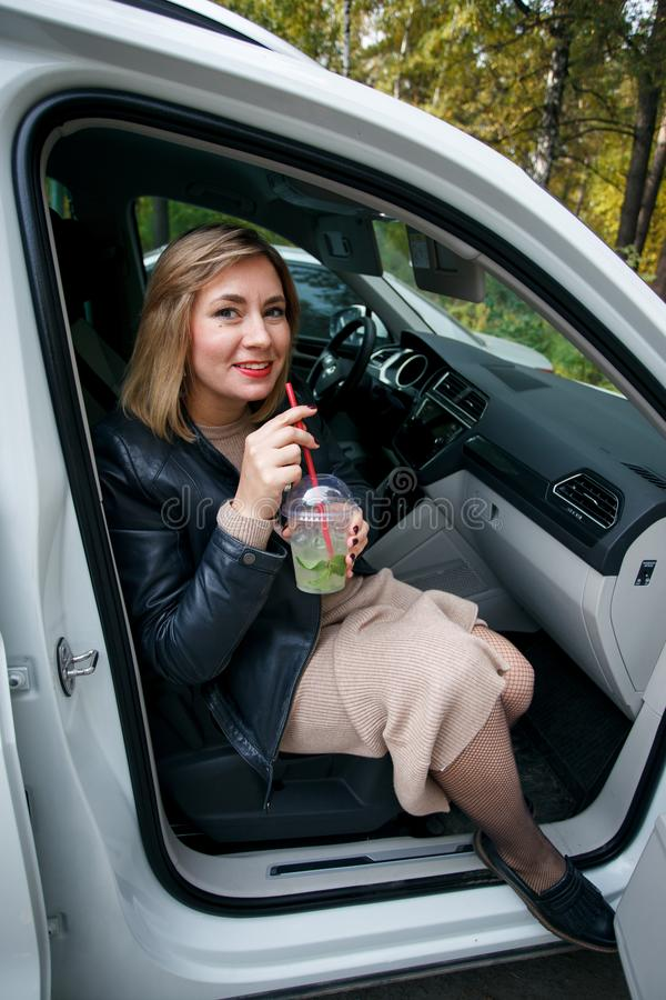 Gravidez, maternidade e felicidade Fêmea grávida nova à moda que tem o resto seu carro, sentando-se no carro branco Mulher bonita fotografia de stock royalty free