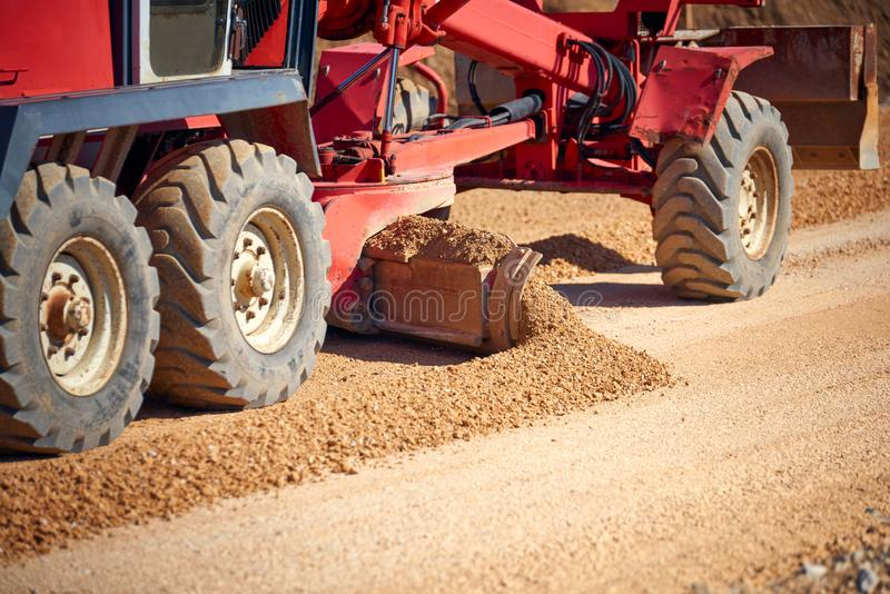 Gravier de propagation de niveleuse de route sur le site de construction de routes - vue de plan rapproché photographie stock libre de droits