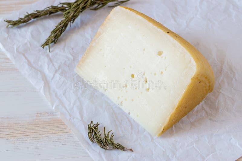 Graviera grec de fromage sur le conseil en bois avec des herbes photos libres de droits