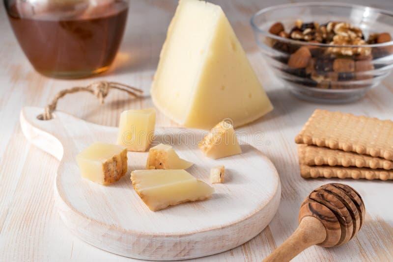 Graviera griego fresco del queso y una rebanada en el tablero de madera blanco foto de archivo libre de regalías