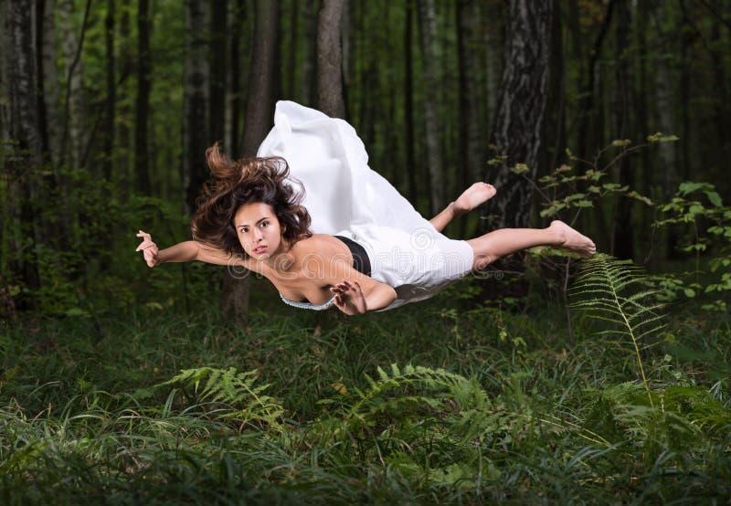 Gravità zero Giovane bello volo della donna in un sogno in una foresta di estate fotografia stock