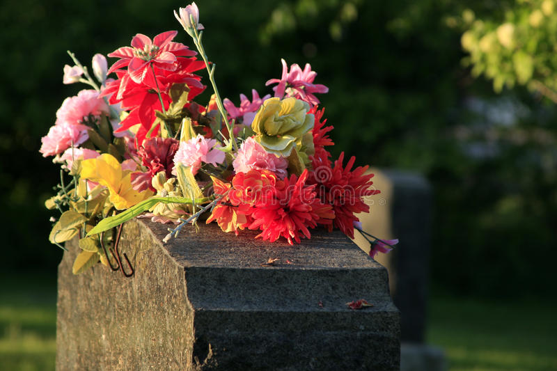 Gravsten med blommor arkivbild
