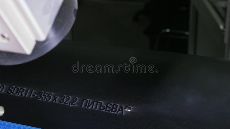 Gravura da máquina da marcação do laser Fabricação de fábrica plástica das tubulações de água Processo de fazer os tubos plástico imagem de stock