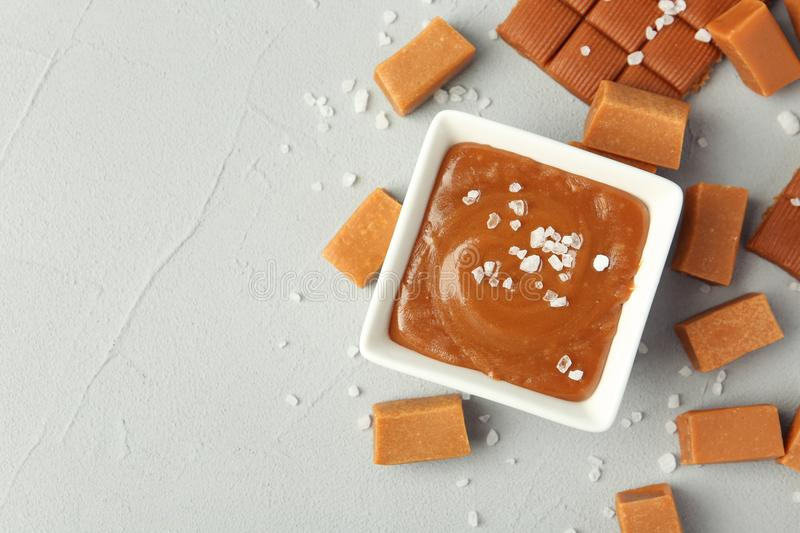 Gravy boat with salted caramel sauce and candies. On table, top view stock photography