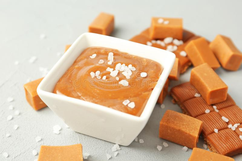 Gravy boat with salted caramel sauce. And candies on table stock image