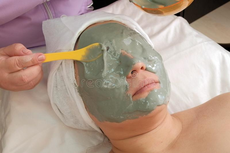 Gray alginate mask on the face of an Asian woman. The hands of a beautician put a lot on the face of the client. Skin lifting. stock photography