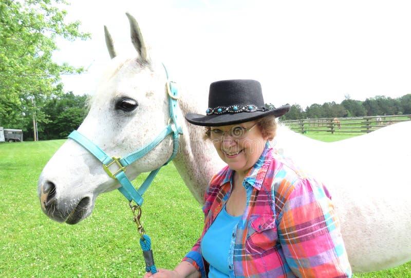 Gray Arabian-Pferd mit älterer Frau lizenzfreie stockbilder
