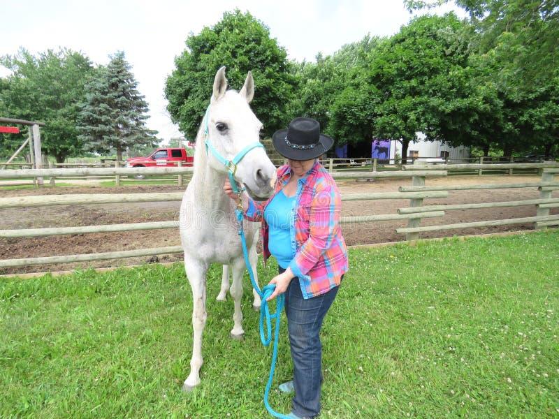Gray Arabian-Pferd mit älterer Frau lizenzfreies stockfoto