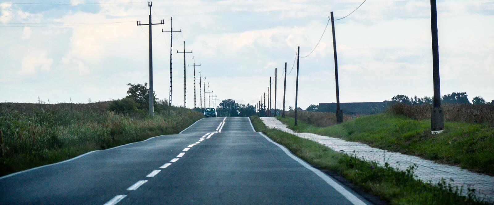 Gray Asphalt Road Between Green Grass and Gray Electric Post during Daytime royalty free stock images