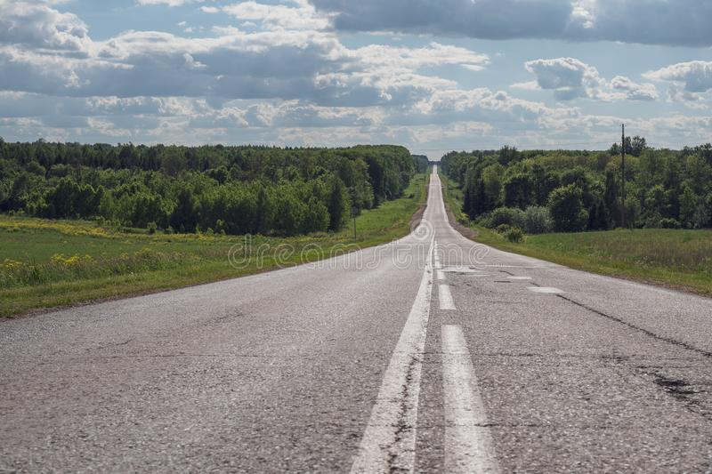 Gray asphalt road with white markings going into the horizon, the concept of life, achieving goals, strong character.  stock photo
