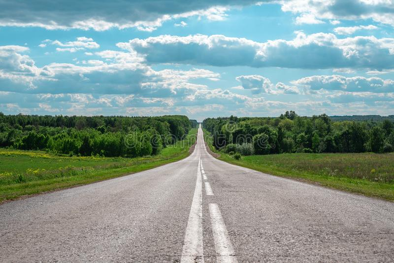Gray asphalt road with white markings going into the horizon, the concept of life, achieving goals, strong character.  stock images