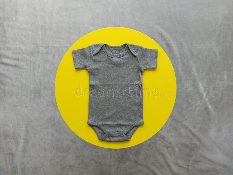Gray baby bodysuit mockup on a yellow circle - blank for own design royalty free stock photos