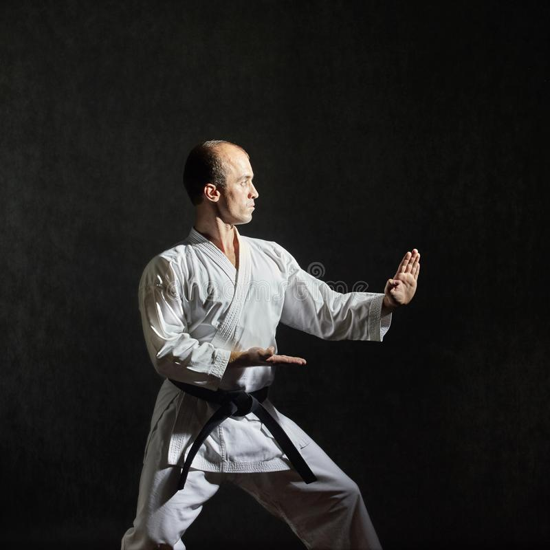 On a gray background, an athlete with a black belt trains a formal exercise karate stock images