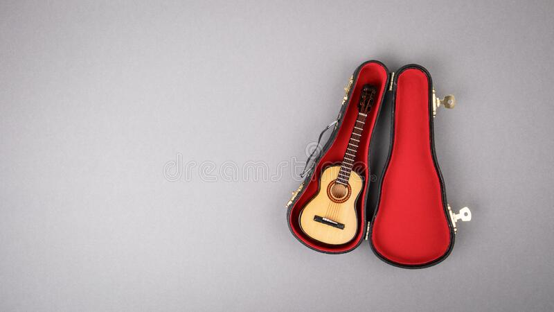 Gray background with copy space. Wooden Guitar with black Box royalty free stock image