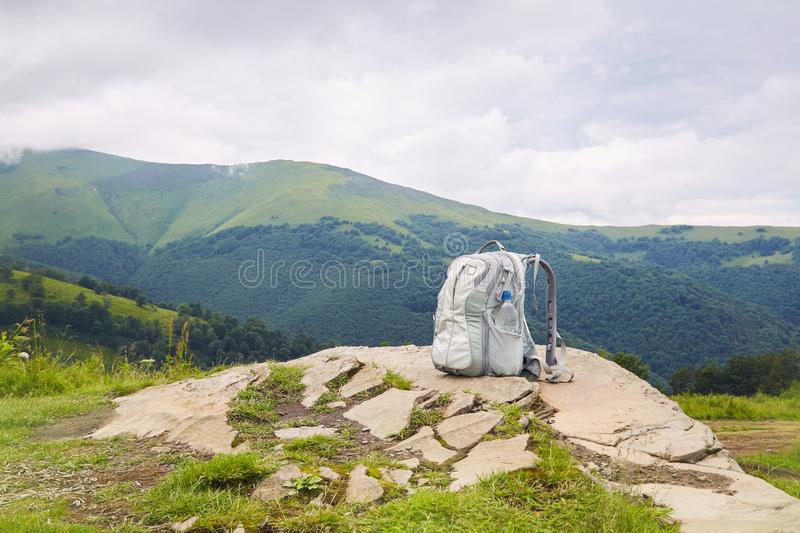 Gray backpack with a plastic bottle of drinking water on top of a mountain stock photo
