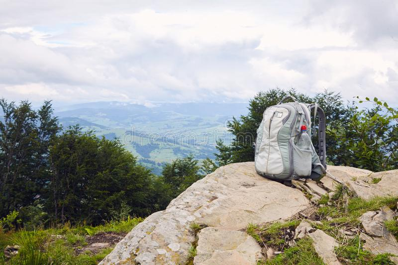 Gray backpack with a plastic bottle of drinking water on top of a mountain royalty free stock photos