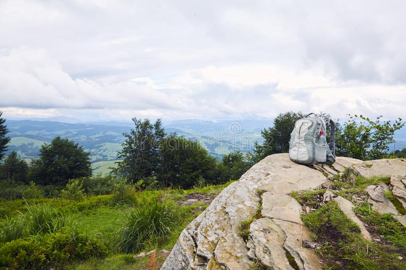 Gray backpack with a plastic bottle of drinking water on top of a mountain stock images