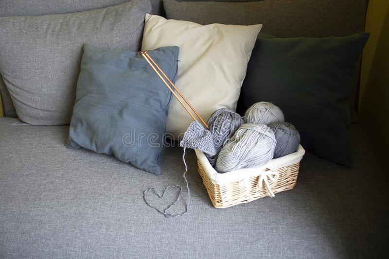 Gray balls of wool and knitting needles in a basket stand on a gray sofa with pillows royalty free stock photo