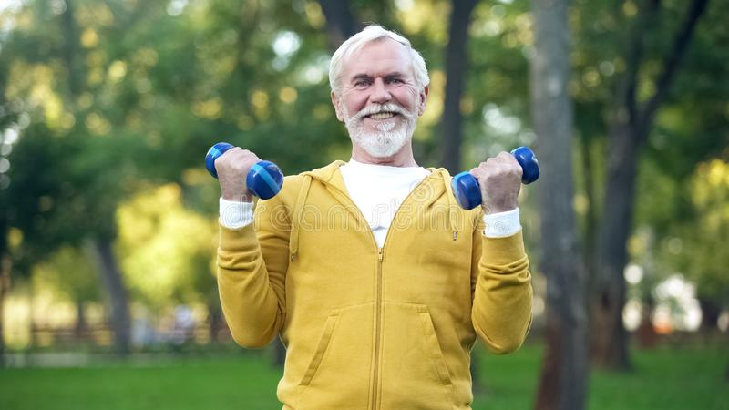 Gray-bearded man lifting dumbbells in park, leisure activity, healthcare royalty free stock photography