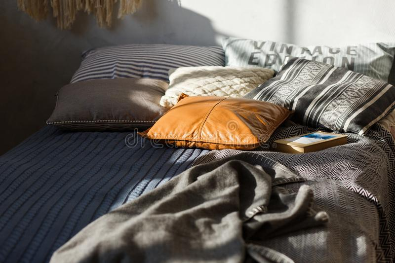 Gray bed, colored pillows and textured wall in the background. Close-up shot, focus on leather pillow.  royalty free stock photos