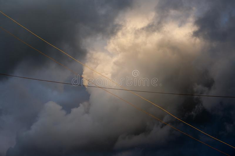 Gray big cloud against sky. With electric wires stock photography