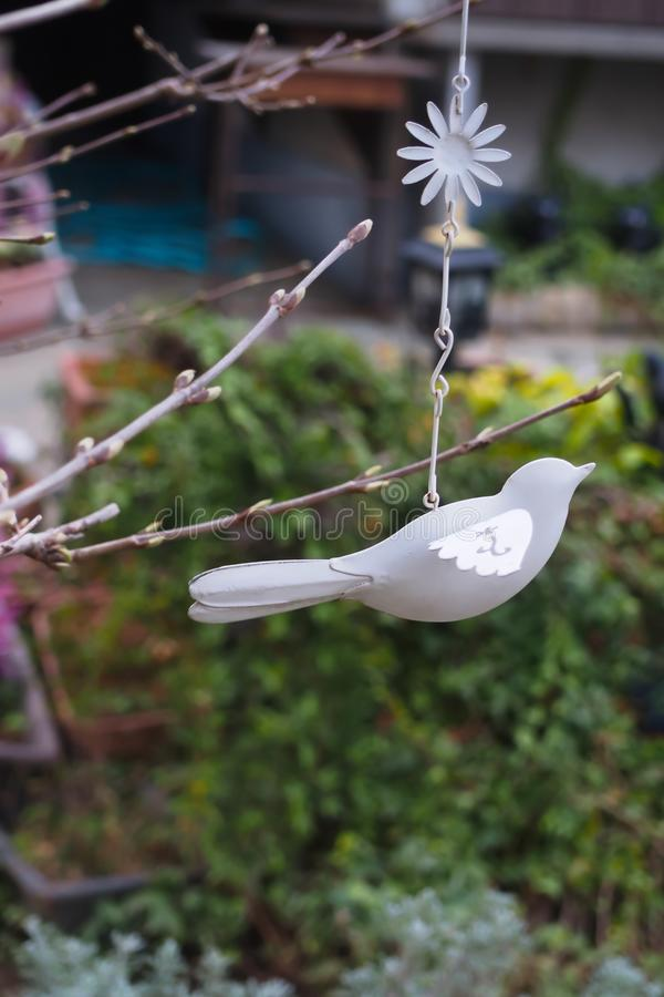 Gray bird mobile decorated on the branches in the garden stock photo