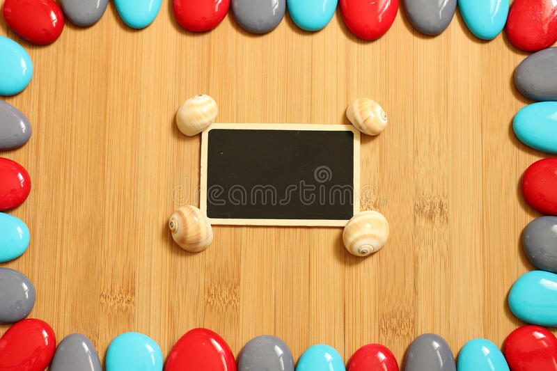Gray and blue red pebbles arranged all around a floor of brown bamboo wood with in the center a small empty slate to write a stock photo