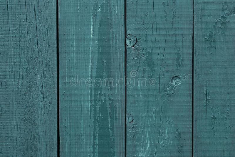 Gray-blue wooden fence rough wood. Wooden fence cracked paint. Rough wooden boards painted gray-blue. Wood texture background, oak stock photo