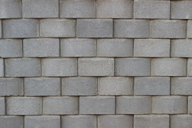 Background pattern wall stone gray block brick. Gray brick stone wall for a background photographed frontally with cement layers stock photography