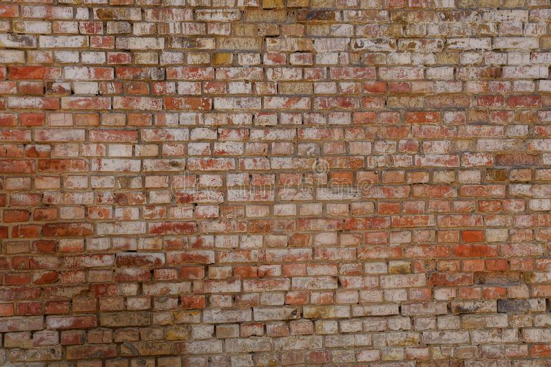 Gray brown texture of a brick in an old wall. Gray brown background of bricks in an old building wall stock photo