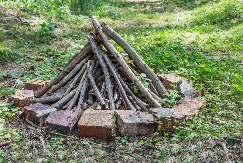 Gray and brown firewood for a bonfire are in a round fire with orange bricks on green grass in a summer forest. like a pyramid. Gray and brown firewood for a stock images
