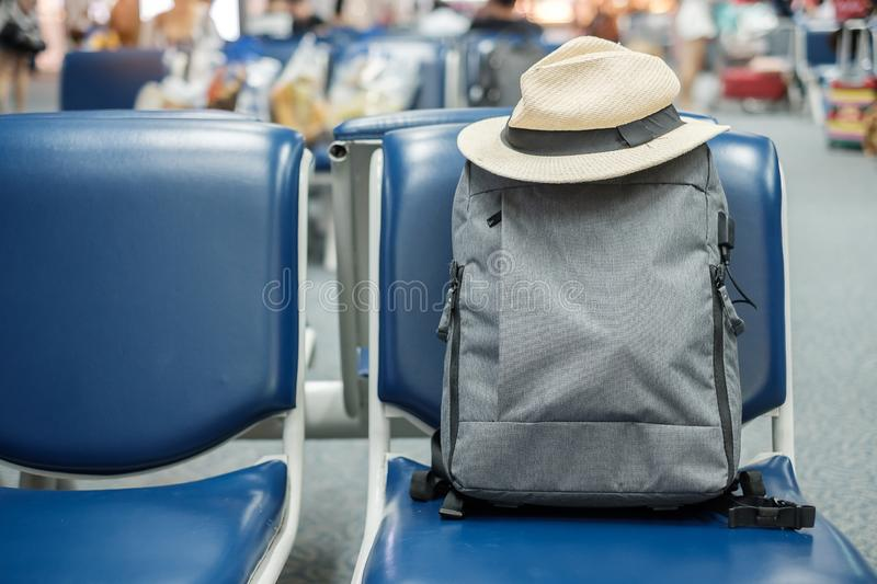 Gray business backpack with hat on seat at the interior of airport terminal. Business and Travel concept stock photography