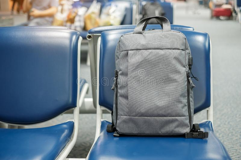 Gray business backpack on seat at the interior of airport terminal. Business and Travel concept royalty free stock photo