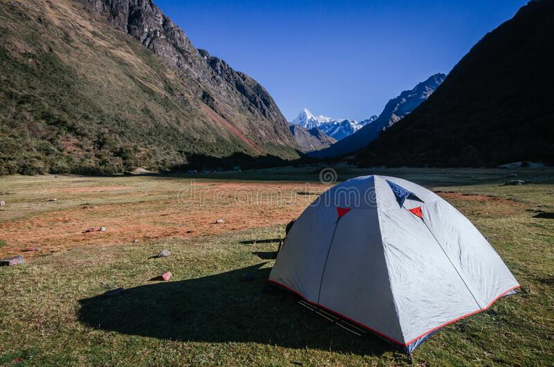 Gray camping tent with high snowy mountains in the background, on the trekking of the quebrada santa cruz. In peru stock photography