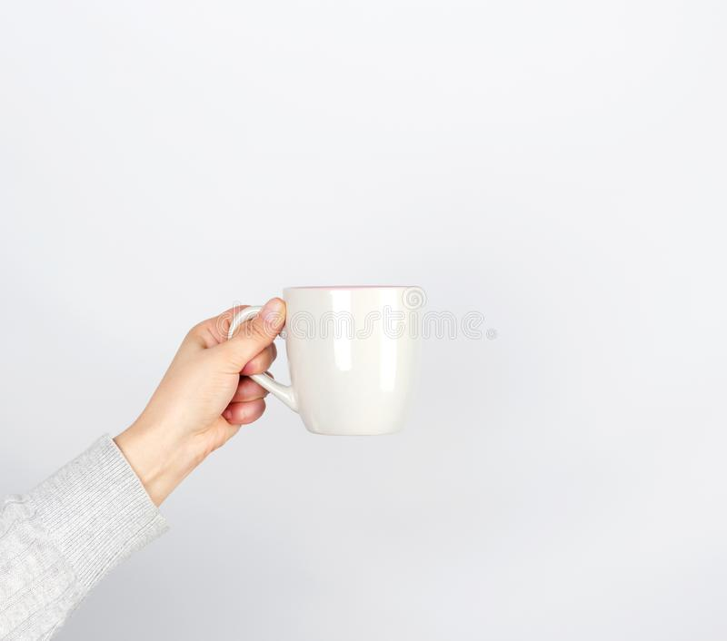 gray ceramic cup in female hand on a white background royalty free stock photos