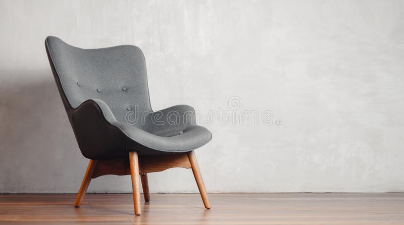 Gray chair in white concrete room for copy space. Concept of minimalism stock photos