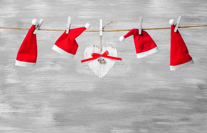 Gray christmas background with santa hats on a rope and wooden heart. Gray christmas background with santa hats and heart on a rope royalty free stock image