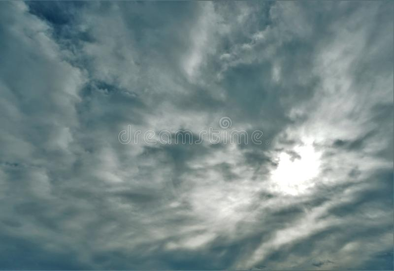 Gray clouds and bright central spot. Darkening gray clouds billow through a brighter sky in the background stock photography