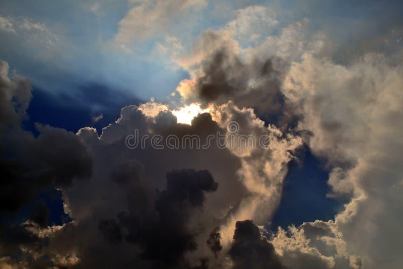 Gray Clouds Cover Sun Under blå himmel royaltyfri foto